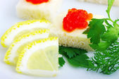 Sendviče s červeným kaviárem a zelení na bílé plotně