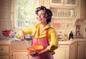 Casalinga sorridente, preparare il cibo in cucina