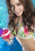 žena s koktejlem v bazénu