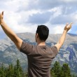 thumbnail of Man standing in nature with arms lifted up