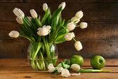Bílé tulipány v skleněná váza na rustikální dřevo