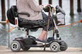 Vezető nő a tengerparton, a mobilitás scooter