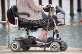 Starší žena u moře na mobilitu scooter