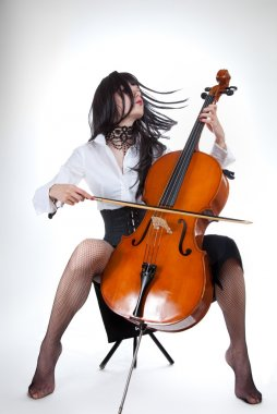 Sensual girl playing cello and moving her hair