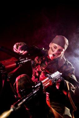 Screaming soldier shooting his enemies, studio shot over black background stock vector