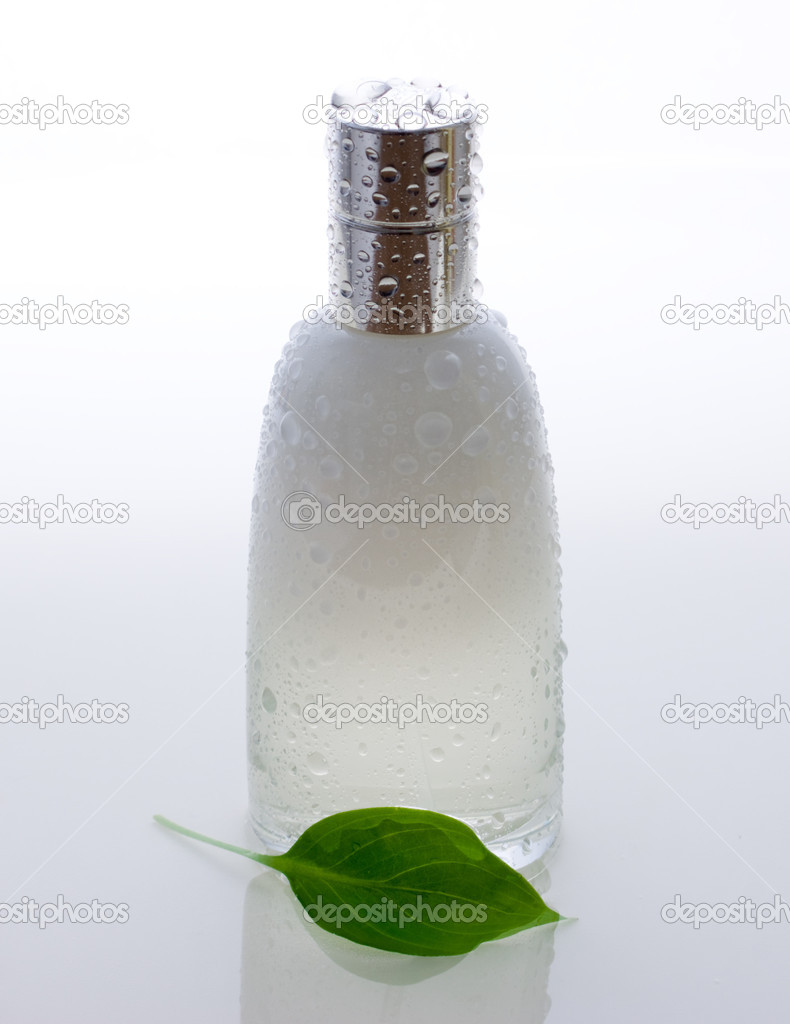 Perfume bottle and green leaf with drops