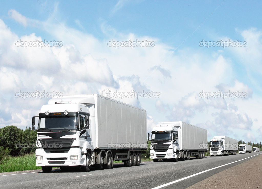 Caravan of white trucks on highway