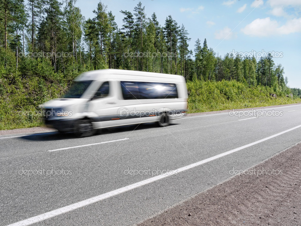 White mini bus speeding on country highway, motion blur
