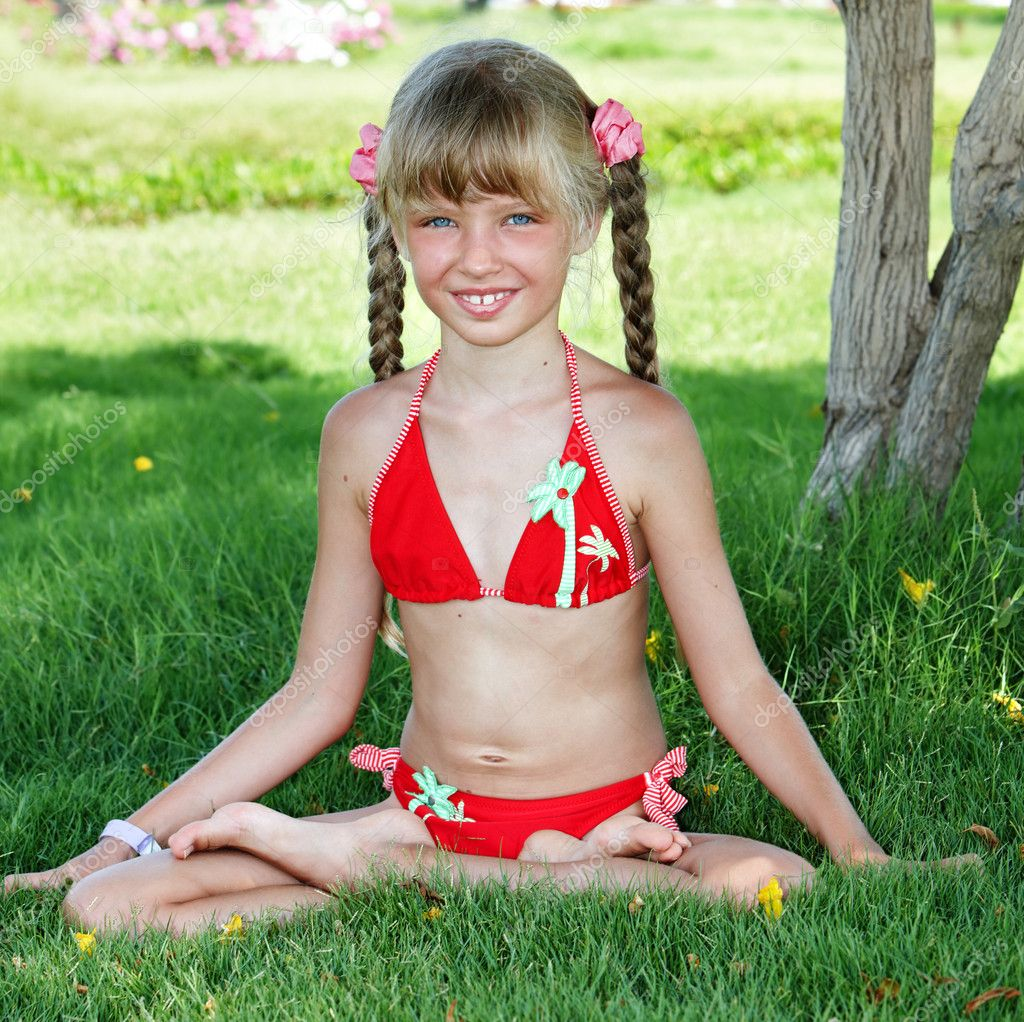 Little girl sit in lotus position and meditate.