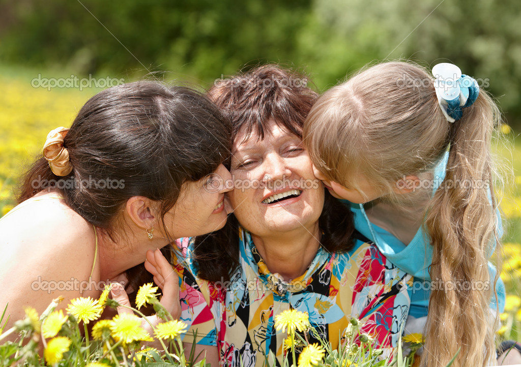 Grandmother with daughter and granddaughter outdoors.