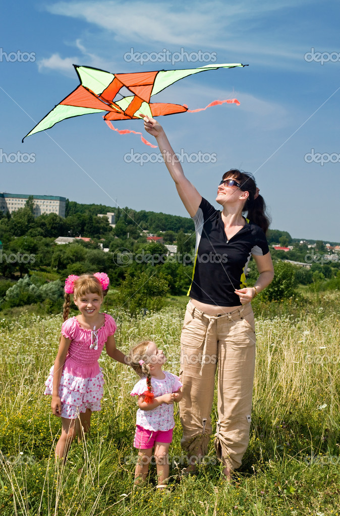 Happy family and children fly kite.