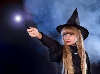 Girl in witch's hat with magic wand