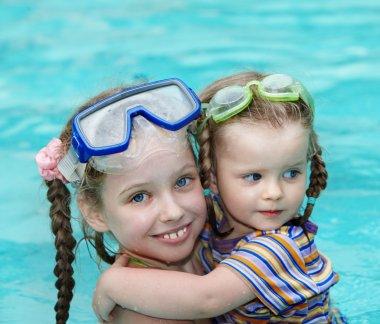 Children swim in swimming pool.