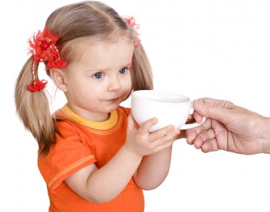 Baby in orange drink cup of milk.