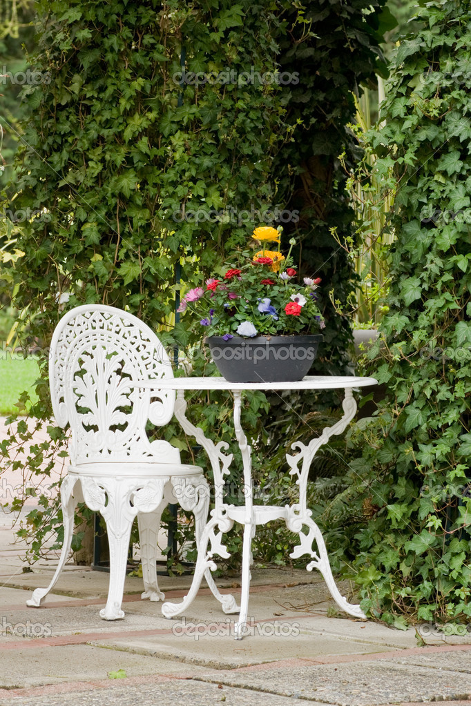 White Wrought Iron Table And Chairs Part - 39: A White Wrought Iron Table And Chair Sit In A Garden Setting U2014 Photo By  Eppic