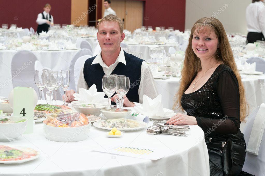 Liefdevolle jong koppel in restaurant aan ronde witte tafel. diner