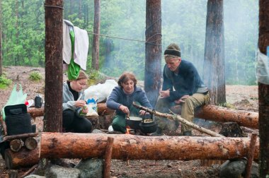 Hikers cook on fire in forest