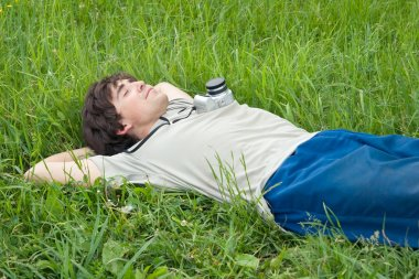 Young man resting on green grass with a photocamera stock vector
