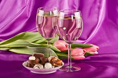 Glasses of wine, flowers and sweets