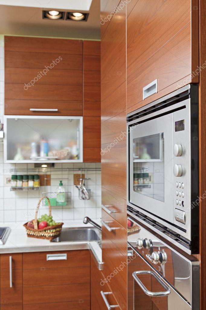 parte dell\'interno di cucina con mobili in legno e costruire in micr ...
