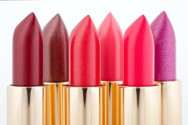 Multicolored color lipsticks arranged in two lines isolated on w