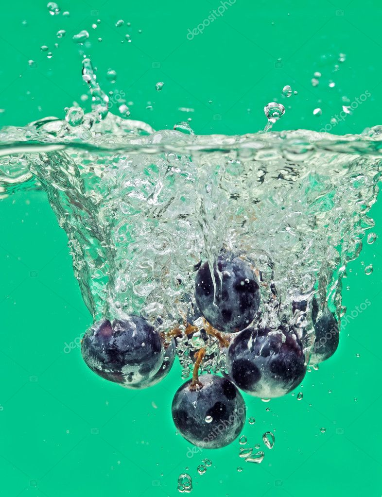 Bunch of grapes floating in water with air bubbles