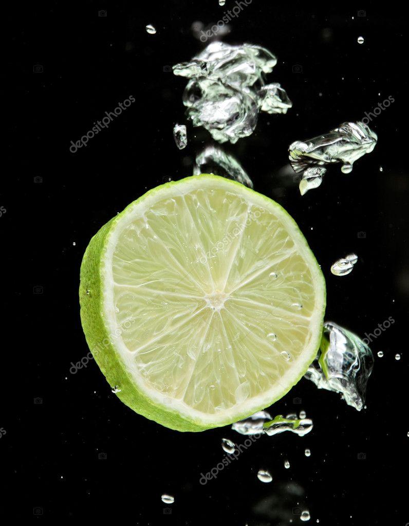 Lime (lemon) falling in water on black