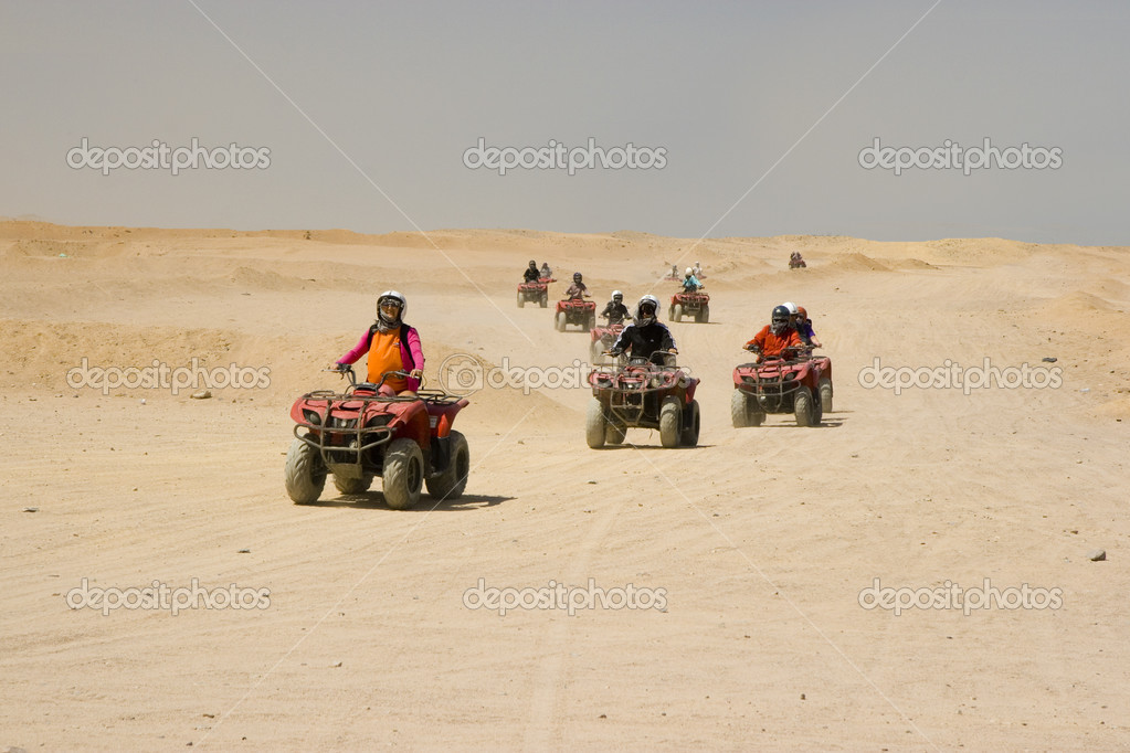Race on quad in desert