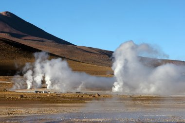 Geyser field with volcano in background