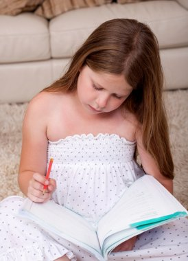 Young school girl reading book in living room