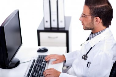 Male doctor working with desktop at his desk