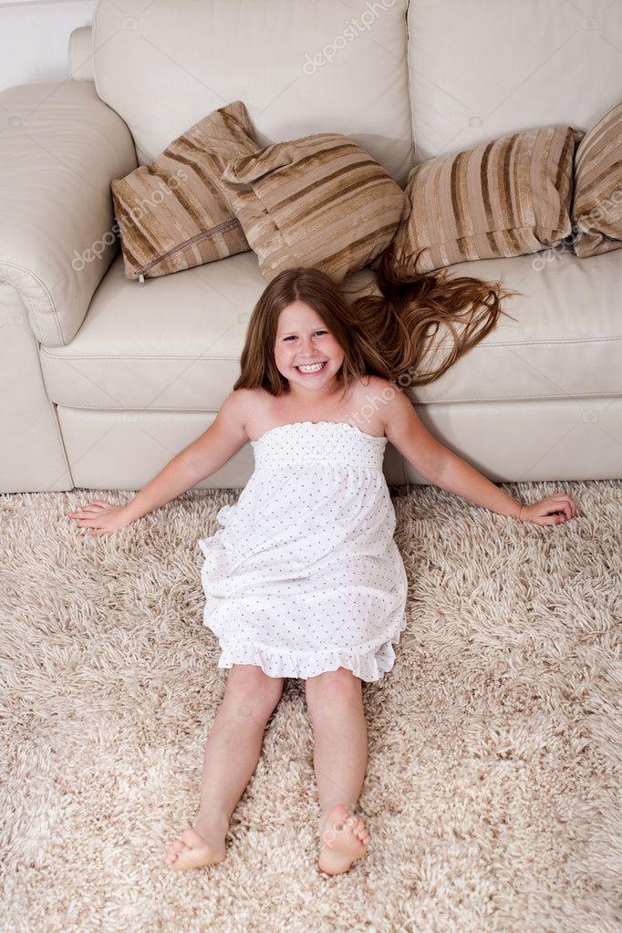 Beautiful little girl sitting on carpet