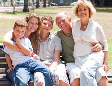 Happy family sitting on park bench