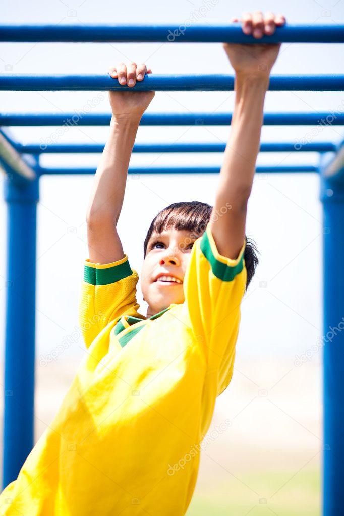 Smart unge spelar på klätterställning — Stockfoto · Fotboll pojke ha kul  som han korsar på djungeln gym bb3efb58710c6