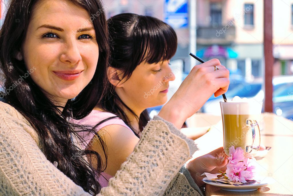 Two girls drinking cappuccino