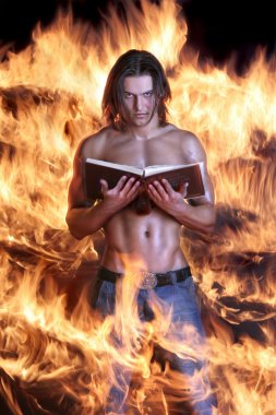 Brawny the man holds the book and burns on fire