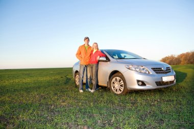 Happy young couple with new car