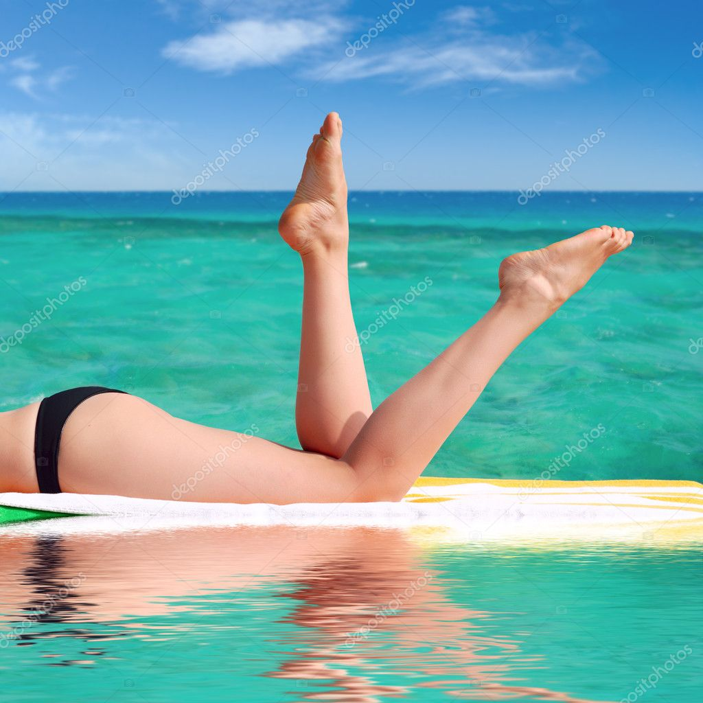 Sexy female legs against the turquoise sea backg