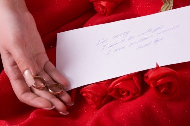 Parting note. Woman hold wedding rings