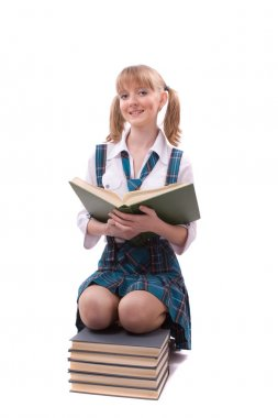 Schoolgirl is sitting on the stack of book and reading.