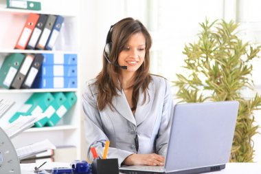 Portrait of a beautiful business woman working at her desk with a headset a