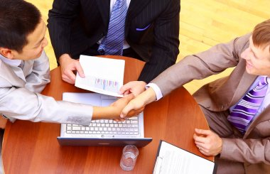 Business handshake over workplace