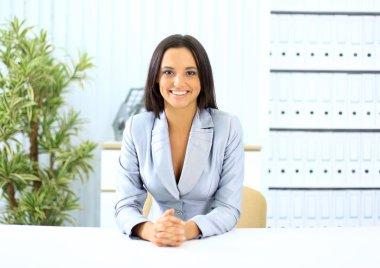 Portrait of pretty girl sitting at desk in bright office