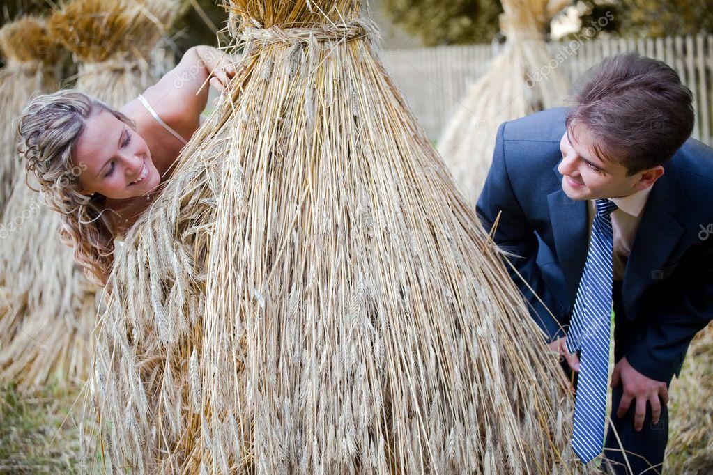Wedding couple behind hay stack