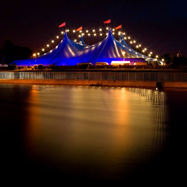 Circus style blue tent and row of lights at night
