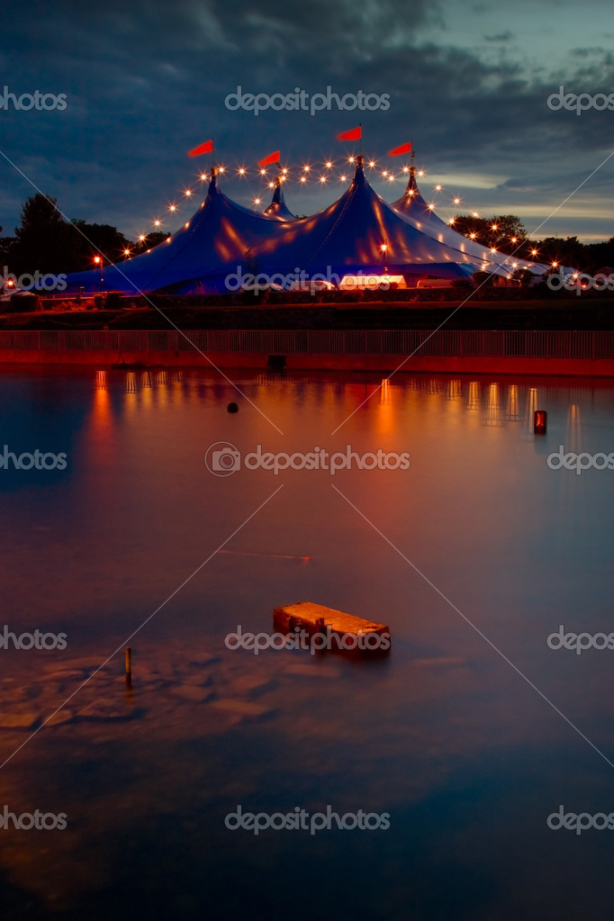 Big Top  circus style blue tent and row of lights on the bank of Corrib river in Galway Ireland u2014 Photo by rihardzz & Circus style tent with lights reflected in river u2014 Stock Photo ...