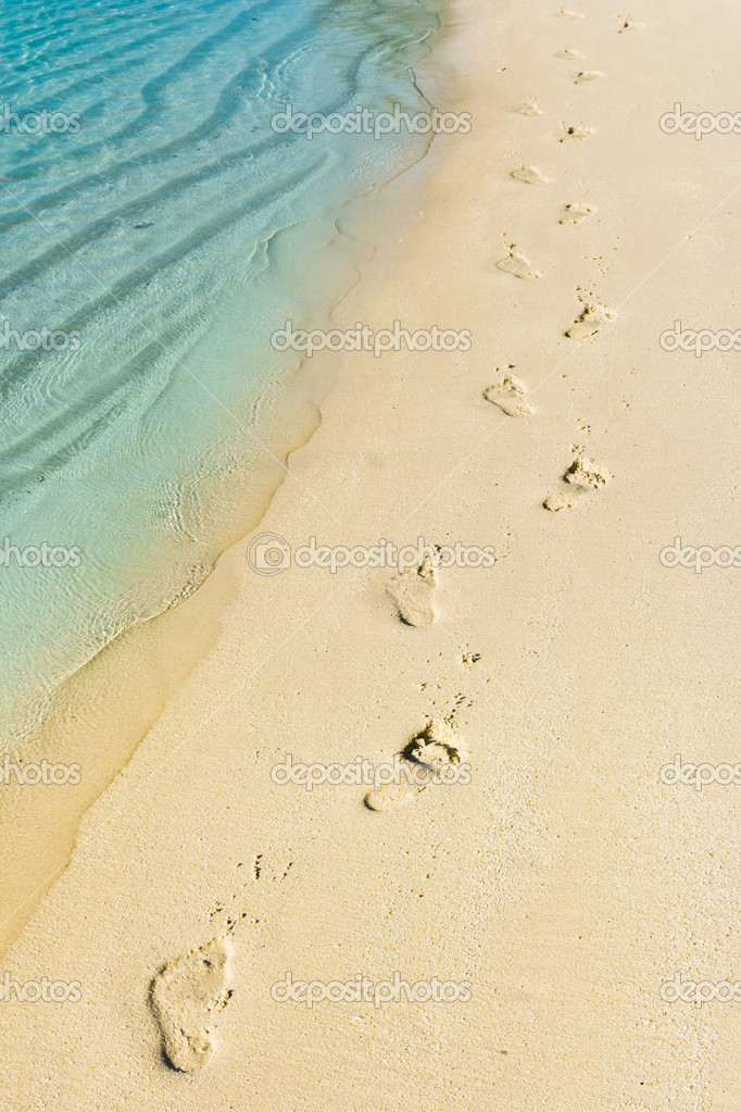 Foot steps and surf on tropical beach