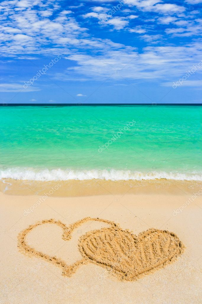 Drawing connected hearts on beach