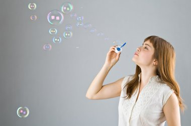 Young beautiful girl catch soap bubble
