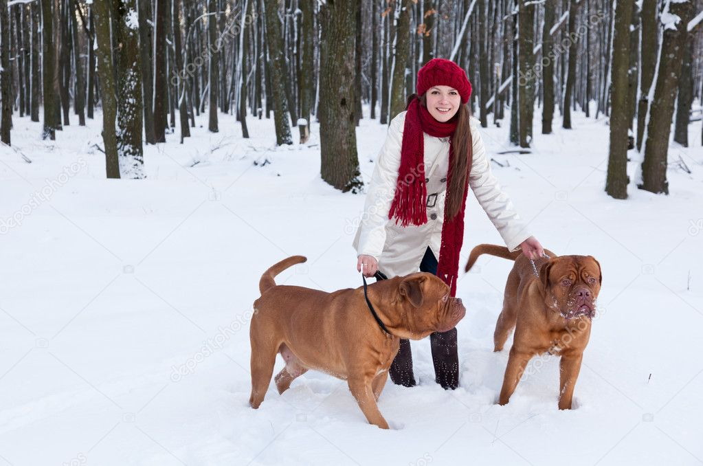 A beautiful woman is walking in the park with her dogs